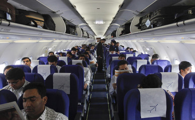 Passengers sit inside an Indigo Airlines A320 aircraft before it takes off from Bengaluru International Airport in Bangalore