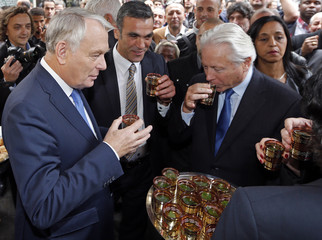 French Prime Minister Ayrault drinks a glass of tea with president of the Marseille Urban Community Caselli in front of a Tunisian pastry shop during a visit