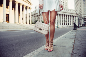 Closeup details of summer female casual street style outfit with luxury bag, skirt and high-heels. Fashionable girl standing at New York City street. Wall mural
