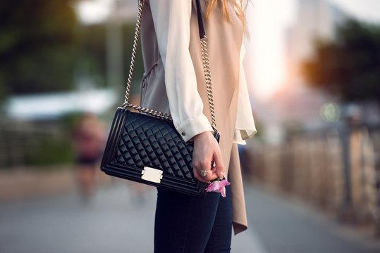 Close up of stylish female black leather bag outdoors. Fashionable and luxury style expensive female bag.