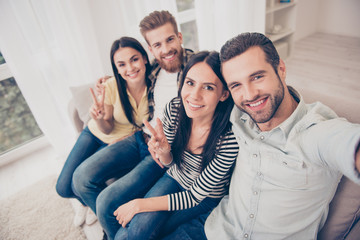 Close up top view of happy friend`s selfie photo, taken at home indoors. They are posing, smiling and showing two fingers sign, all wearing casual outfits