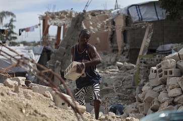 A man carries a slab of rock from a destroyed house in Port-au-Prince