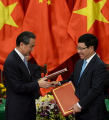 Wang and Minh exchanged signed documents in Hanoi