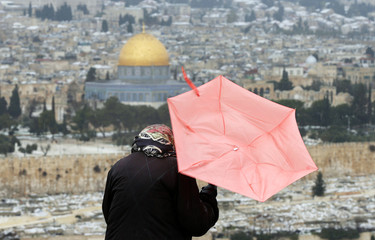 The Dome of the Rock is seen in the background as a tourist holds her umbrella outside Jerusalem's Old City
