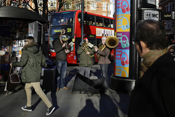 Three men play brass instruments on a busy shopping street in Chelsea