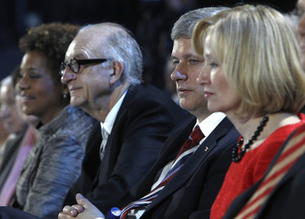 Canada's PM Harper and his wife Laureen Ann sit with Jean, Governor General of Canada, and her husband Jean-Daniel Lafond during the opening ceremony of the Vancouver Winter Olympic Games in Vancouver