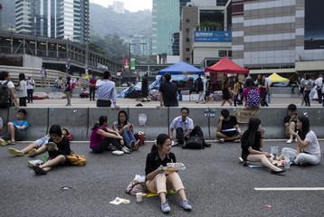 A woman takes her lunch while sitting on a highway, part of an area blocked off by protesters of the Occupy Central movement, in Hong Kong