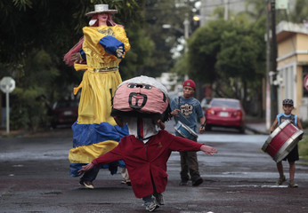 "A boy in a costume dances next to a performer dressed as ""La Gigantona"" along a street in Managua"