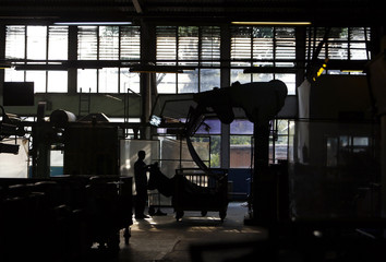 Worker holds textile to check the quality at PT Trisula International in Bandung