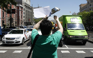 A striking teacher bangs a pot during a protest in front of the education ministry in Madrid during a general education strike