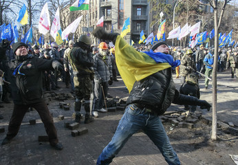 Anti-government protesters throw stones towards Interior Ministry officers during a rally near the building of Vekhovnaya Rada, Ukraine's house of parliament, in Kiev
