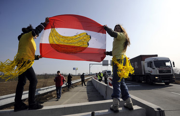 Slovak and Czech human rights activists hold Austrian national flag with picture of banana on it during 15-minute blockade on Slovak-Austrian border crossing in Bratislava-Jarovce