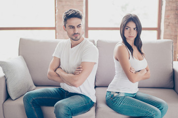 I am not talking to you! Mistrust and cheat problems. Annoyed couple is ignoring each other, sitting on the couch back to back indoors at home