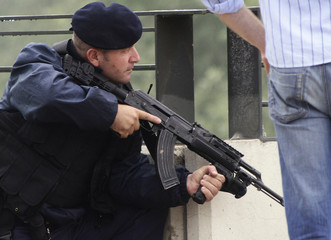 A Kosovo local police officer holds an automatic weapon during a violent protest in the divided town of Mitrovica