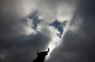 """A billboard-size figure of a bull, known as the """"Osborne Bull"""", is silhouetted against a cloudy sky in Torremocha del Campo"""
