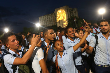 Students pose for selfies as they attend a massive tribute to Cuba's late President Fidel Castro in Revolution Square in Havana