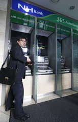 A customer leaves after drawing money from the ATM at a branch of Nonghyup Bank in Seoul