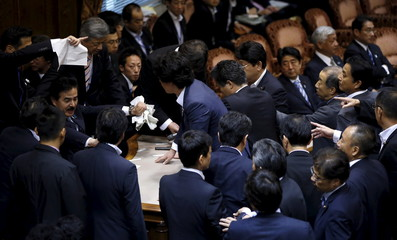 Opposition lawmakers crowd around Sato, deputation chairman of the upper house special committee on security, as Japan's PM Abe looks on at an upper house special committee session on security-related legislation at the parliament in Tokyo