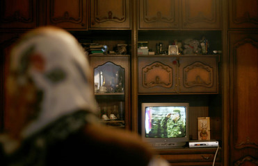 Malic Zuhra, a Muslim woman watches a news program on television flashing images of wartime General Ratko Mladic in Potocari near Srebrenica