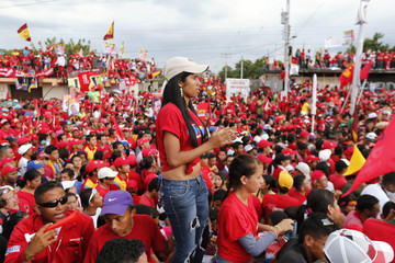 Supporters listen to Venezuela's President Chavez during a campaign rally in Acarigua