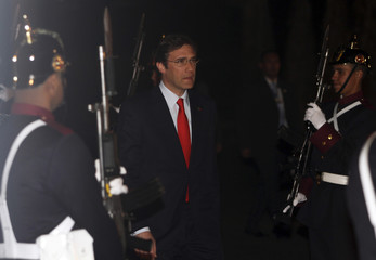 Portugal's Prime Minister Pedro Passos Coelho reviews the guard of honour as he arrives at the presidential palace in Bogota