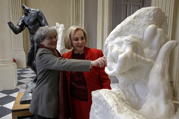 """Musee Rodin Director Catherine Chevillot and US philanthropist Iris Cantor look at Rodin's masterpiece """"La Main de Dieu"""" at the Musee Rodin in Paris"""
