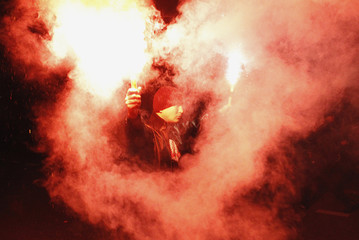 A demonstrator holds flares up as he taunts the riot police as violence breaks out at a parade celebrating Poland's national holiday in Warsaw
