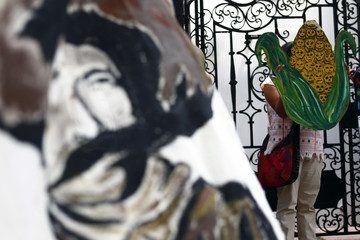 An activist holds a drawing of a maize and skulls next to a banner painted with the image of Emiliano Zapata during a protest against the cultivation of transgenic maize outside U.N OHCHR building in Mexico City