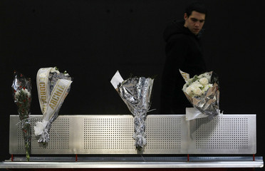 A commuter walks by bouquets of flowers placed at Madrid's Atocha station on the sixth anniversary of the Madrid train bombings