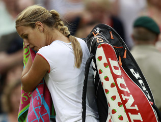 Dominika Cibulkova of Slovakia walks off the court after being defeated by Maria Sharapova of Russia in their quarter-final match at the Wimbledon tennis championships in London