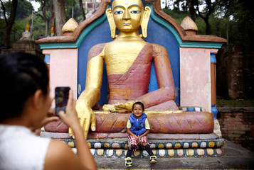 A boy sits in front of an idol of Buddha as a family member takes picture of him during celebrations on the birth anniversary of Buddha, also known as Vesak Day, in Kathmandu