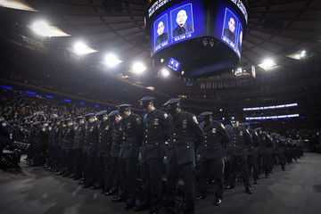 New York Police Department graduates stand in solemn tribute to slain officers Ramos and Wenjian instead of throwing their gloves in the air in celebration in New York