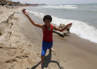 A boy poses with his knife at the seafront in a poor neigbourhood, where he lives at, south of Beirut