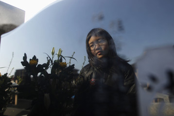 Kumagai is reflected on the grave of her father, who was killed by the tsunami, in Higashimatsushima