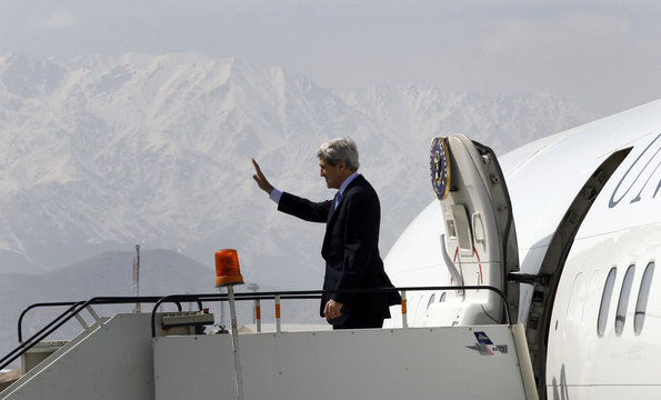 U.S. Secretary of State Kerry waves from the steps of his aircraft with the snow-capped mountains of Afghanistan in the background as he departs Kabul