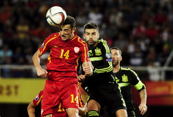 Spain's Pique jumps for the ball with Macedonian Ristevski during their Euro 2016 qualification soccer match at Skopje city stadium