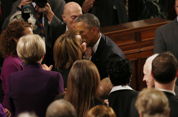 U.S. President Obama kisses U.S. Representative and gun violence victim Giffords as he arrives to deliver his State of the Union address to a joint session of Congress in Washington