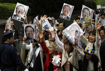 """Supporters of Japan's ruling Democratic Party of Japan powerbroker Ichiro Ozawa holding his portraits shout """"banzai"""" as Ozawa leaves the Tokyo District Court"""