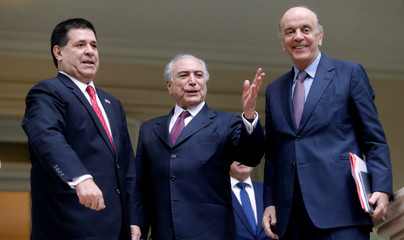 Brazilian President Michel Temer and Brazilian Foreign Minister Jose Serra gestures with Paraguayan President Horacio Cartes during his first official visit to Paraguay, in Asuncion