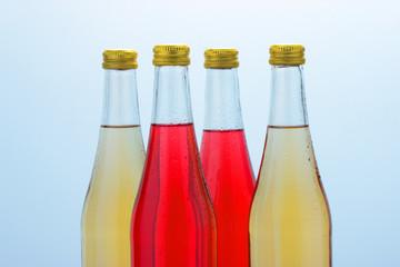 Бутылки с безалкогольными напитками на светлом фоне