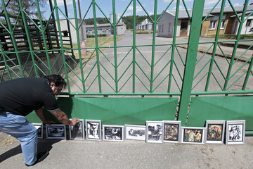 A participant of the European Meeting of Antiracist Leaders places a picture in front of a pig farm, situated at the site of a former Roma concentration camp, to commemorate victims of the Holocaust in Lety