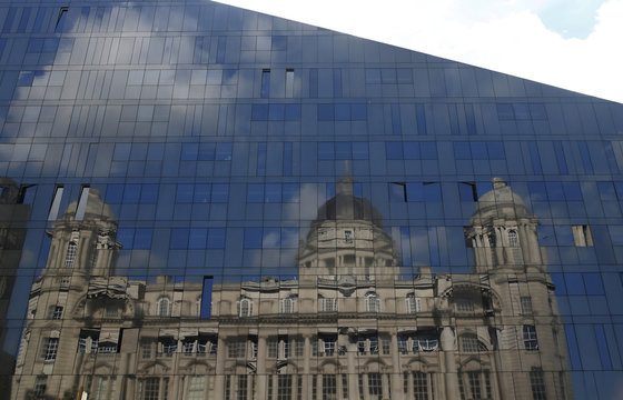 The Port of Liverpool building is seen reflected in the windows of a modern office block in Liverpool northern Britain