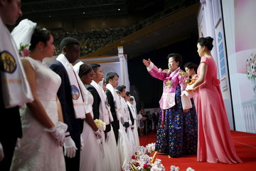 Han Hak-ja sprays holy water to bless newlywed couples during a mass wedding ceremony of the Unification Church at Cheongshim Peace World Centre in Gapyeong