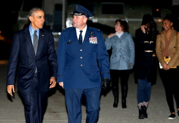 Obama walks with Millard to board Air Force One for travel to Hawaii for his holiday vacation, from Joint Base Andrews, Maryland