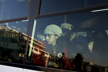 A young undocumented migrant that entered Greece through its sea borders is seen through a bus window at the port of Piraeus, near Athens