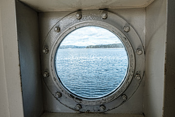 Looking out through a ships porthole onto the water