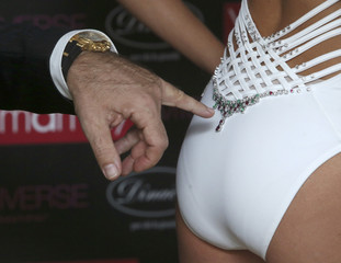 """A participant points to the precious gems on the """"Yamamay Million Dollar Swimsuit For Miss Universe"""" in Moscow"""