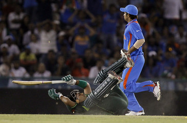 Pakistan's Akmal falls after completing run as India's Raina walks by in background during their ICC Cricket World Cup 2011 semi-final match in Mohali
