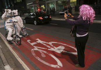 A woman takes a picture of a couple dressed as polar bears with their bicycle and skateboard on a bike lane during World Car-Free Day in Sao Paulo