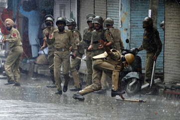 An Indian policeman falls after throwing a piece of stone towards supporters of JKLF, a separatist party, during a protest in Srinagar